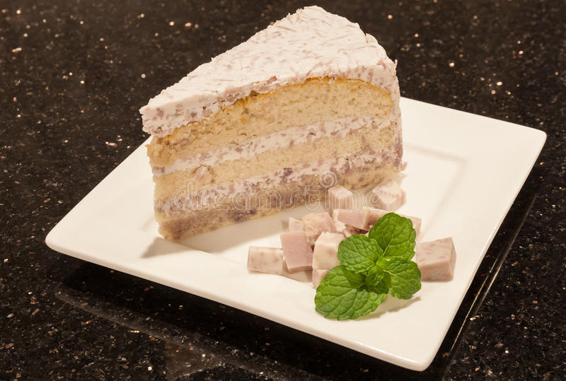 Piece of tasty taro cake served on white square plate. royalty free stock photo