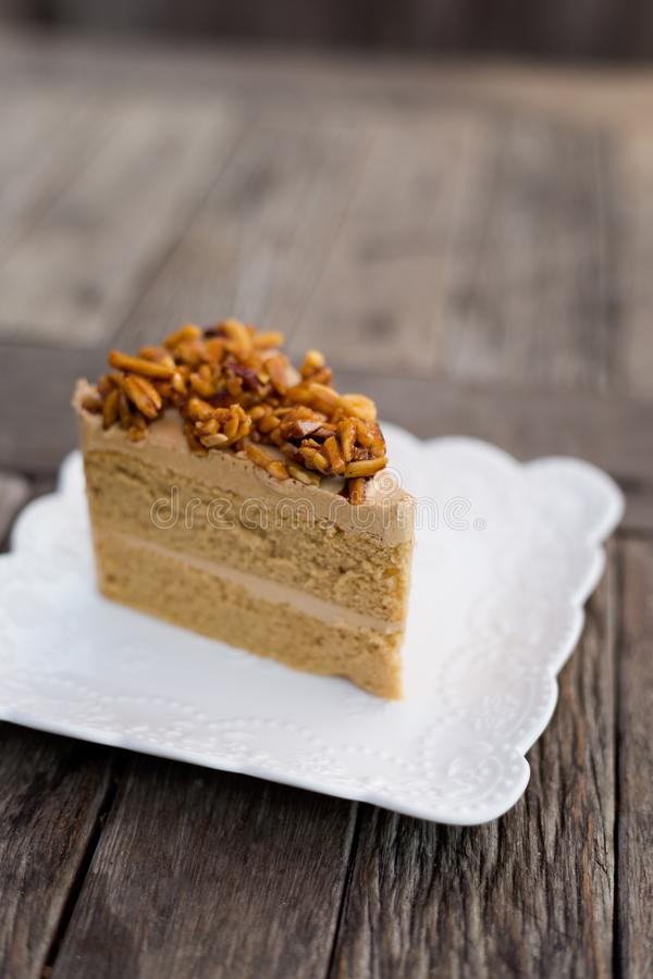 Piece of thai coffee cake. Fresh prepared slice of asian almond coffee cake served in local restaurant. Traditional thai sweets made of fresh ingredients stock photo