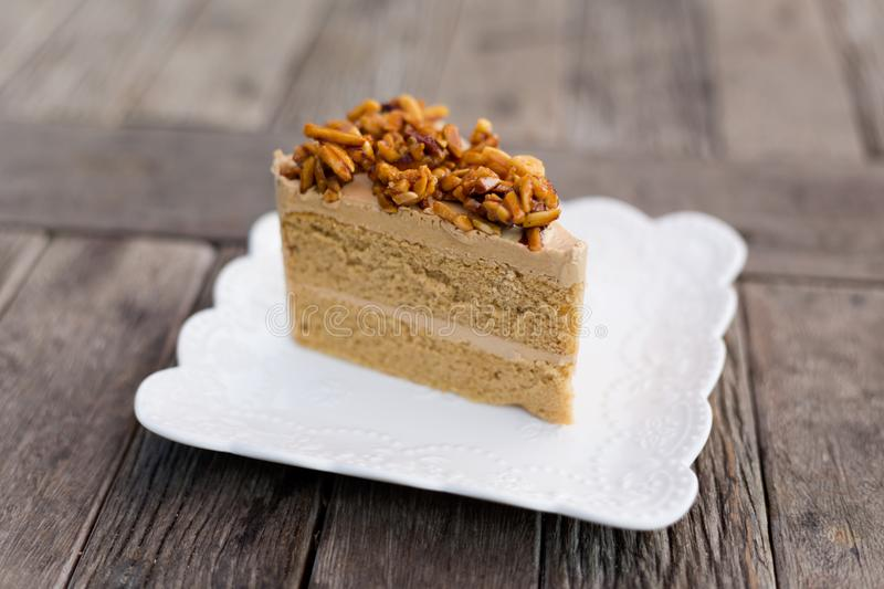 Piece of thai coffee cake. Fresh prepared slice of asian almond coffee cake served in local restaurant. Traditional thai sweets made of fresh ingredients stock photography