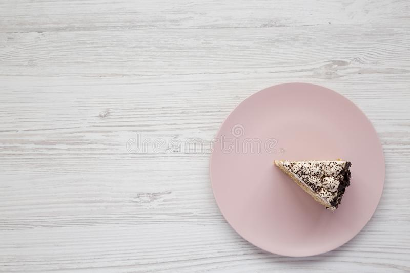 A piece of tiramisu cake on a pink plate on a white wooden background, top view. Copy space royalty free stock images