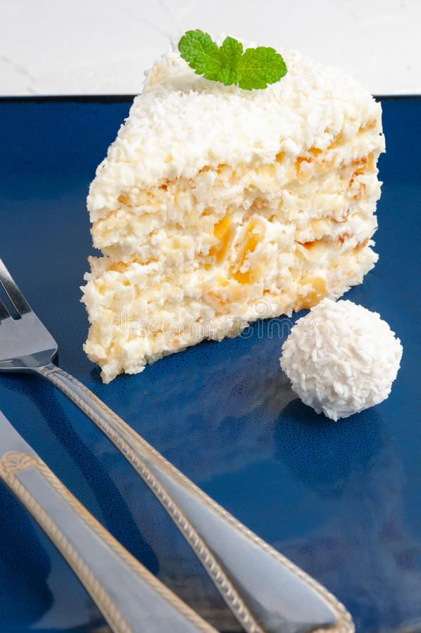 A piece of white cake with almonds and coconut chips on a blue plate. Decorated with mint and candy with coconut. Close-up stock photos