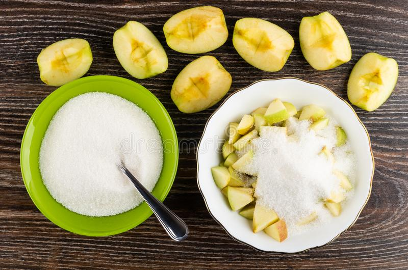 Pieces of apples, bowl with chopped apples, sugar, spoon in bowl with sugar on wooden table. Top view. Pieces of apples, bowl with chopped apples and sugar stock image