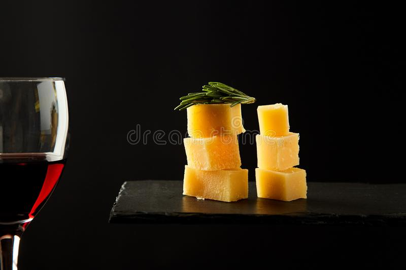Pieces of aromatic cheese on the black board and glass with re wine. royalty free stock photo