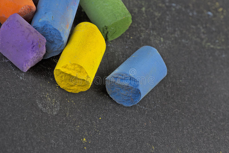 pieces of artist´s colored pastels on black paper surface, macro detail shot, copyspace stock photos