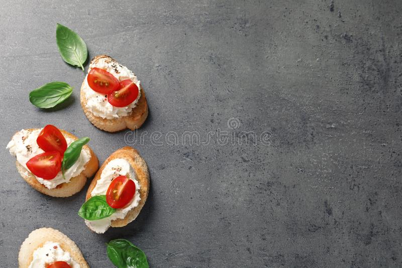 Pieces of baguette with tasty cream cheese and tomatoes on gray table, flat lay. stock photos