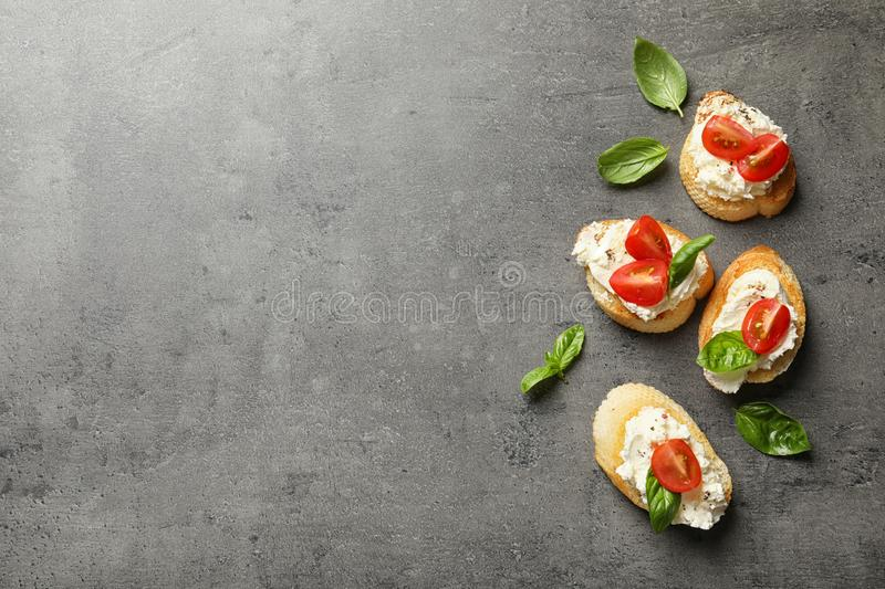 Pieces of baguette with tasty cream cheese and tomatoes on gray table, flat lay. royalty free stock images