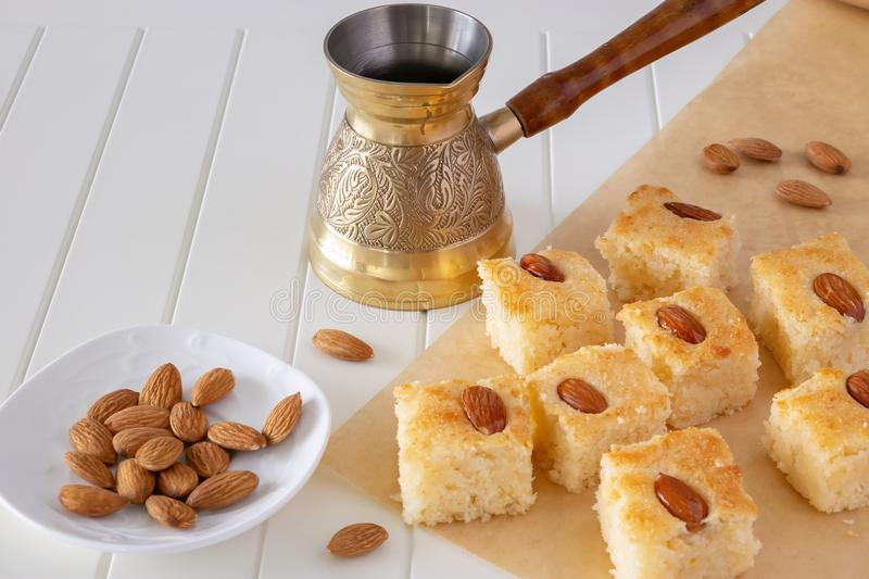 Pieces Basbousa or Namoora traditional arabic sweet dessert with almond. Homemade semolina cake. Copy space. Selective focus. royalty free stock image