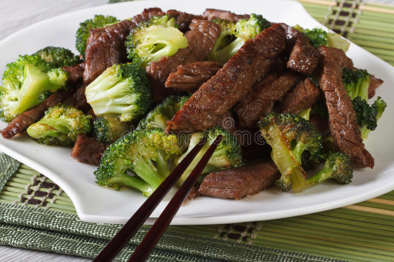 Pieces of beef with broccoli close-up and chopsticks. Horizontal stock photo