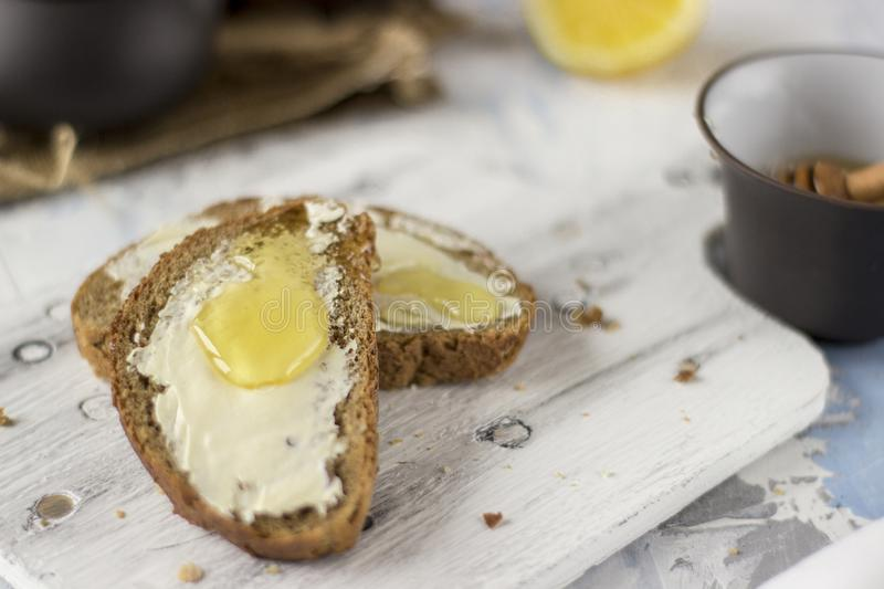 Pieces of bread with butter and honey stock photos