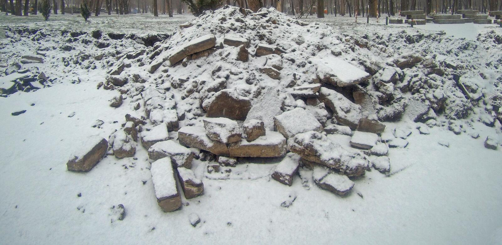 Pieces of broken asphalt covered with snow or ashes stock photography