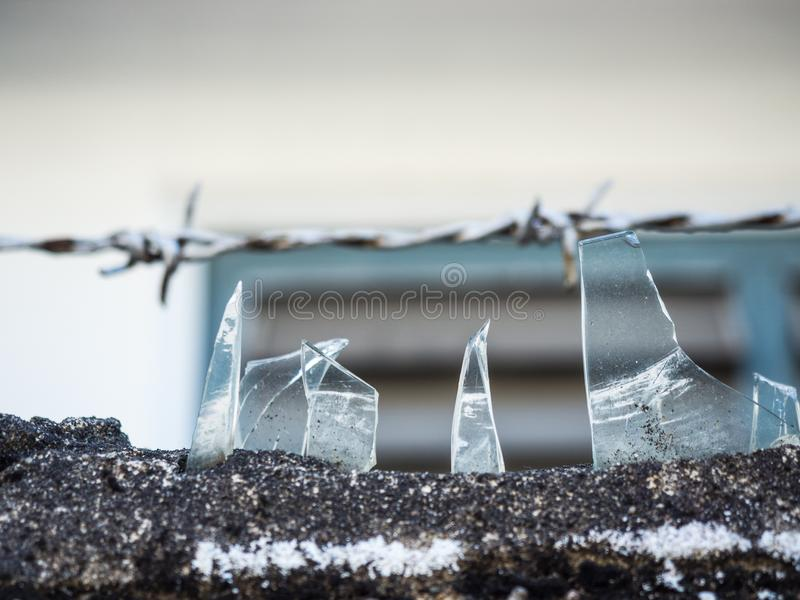 Pieces of broken glass cemented on top of barbed wire fence for protection of any intruder climbing.  royalty free stock photography