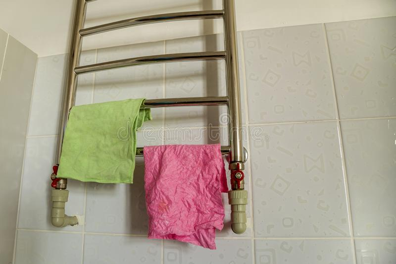 Pieces of cloth drying on bathroom heating towel rail radiator. Towel rack stainless steel shelf.  stock photography