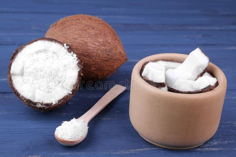 Pieces of coconut in a wooden bowl with a spoon with a whole coconut on a blue wooden background. stock image