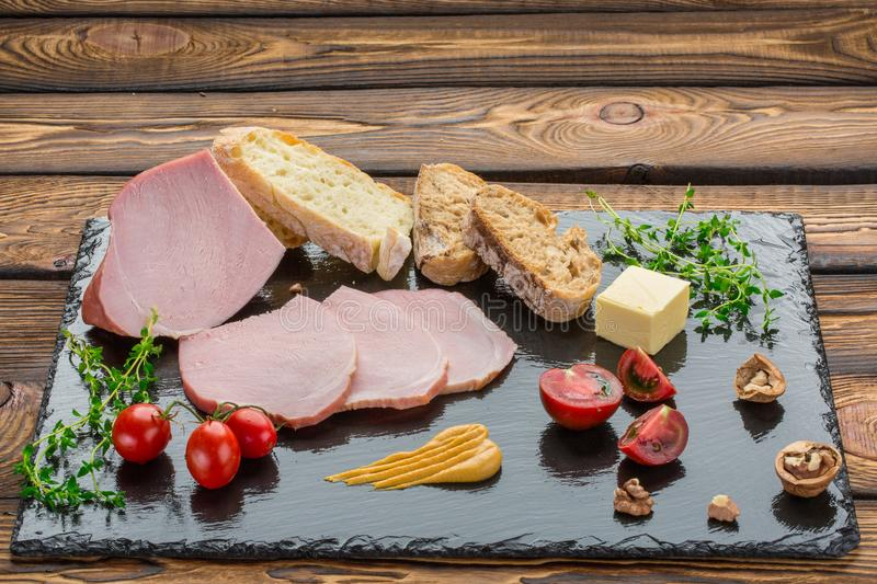 Pieces of cold-boiled, bread, butter, tomatoes, herbs, walnut, mustard. Ingredients for breakfast on black stone board stock photo