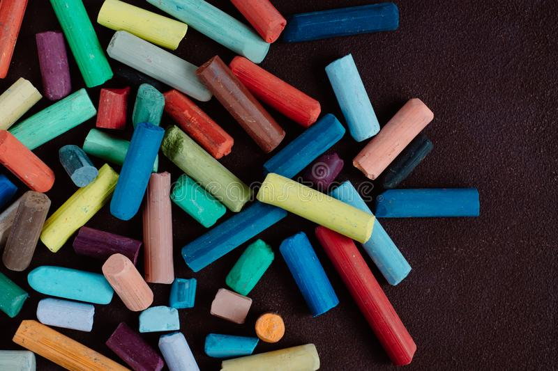 Pieces of color chalk on dark background royalty free stock photography