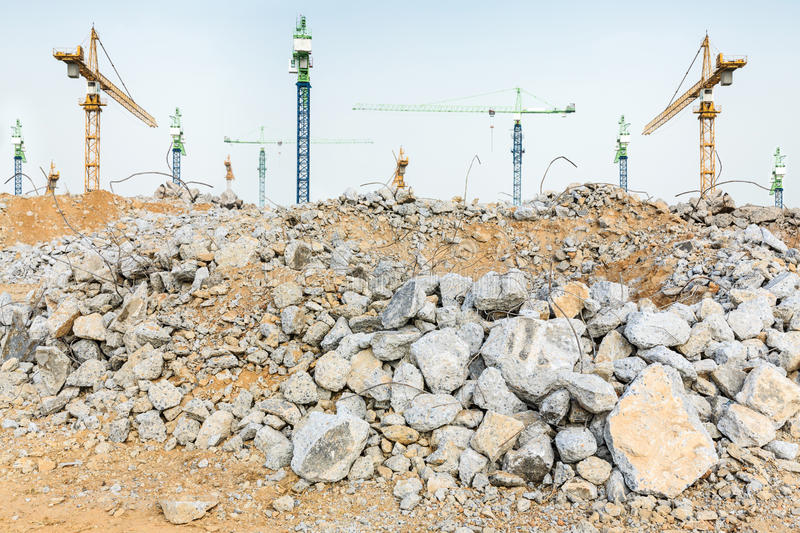 Pieces of concrete and brick rubble debris and giant cranes on construction site stock photo