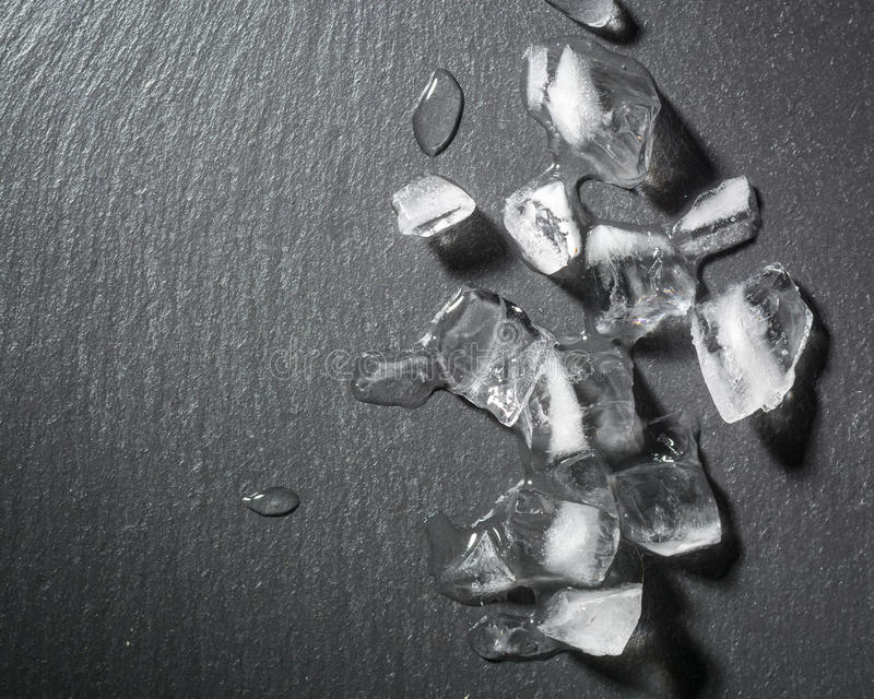 Pieces of crushed ice on a black stone. Drops of water and cold. Dark background royalty free stock photography