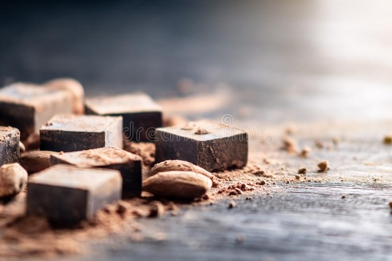 Pieces of dark bitter chocolate with cocoa and almonds nuts on wooden background. Card with space for text. Pieces of dark bitter chocolate with cocoa powder and stock photography
