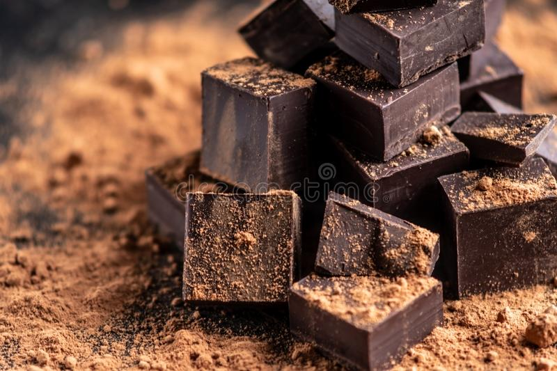 Pieces of dark bitter chocolate with cocoa powder on dark wooden background. Concept of confectionery ingredients. Pieces of dark bitter chocolate with cocoa stock image