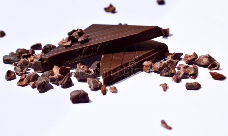 Pieces of dark chocolate and cocoa beans royalty free stock photos