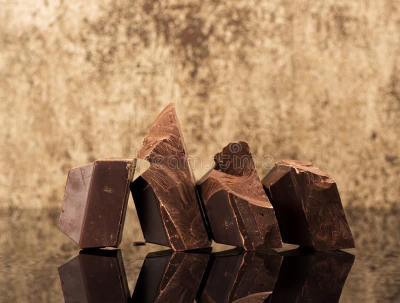 Pieces dark chocolate. On a dark stone background royalty free stock image