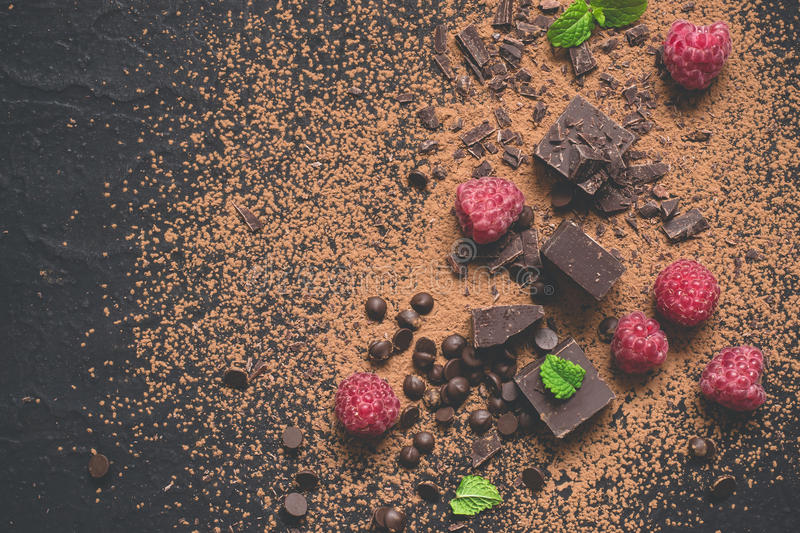 Pieces of dark chocolate, powder, drops and raspberries. Food dessert background. Pieces of dark chocolate, powder, drops and raspberries. Food dessert royalty free stock photography