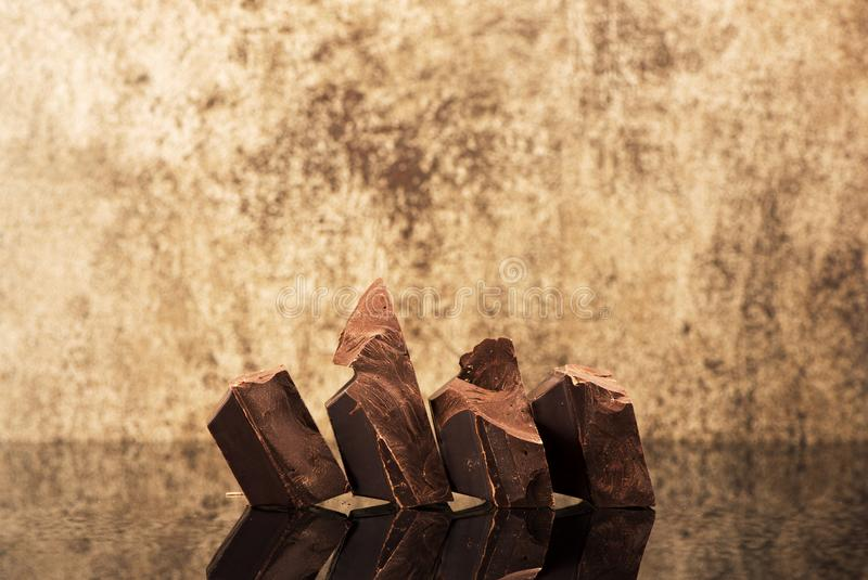 Pieces dark chocolate and space for text. Pieces dark chocolate on a stone background royalty free stock photo