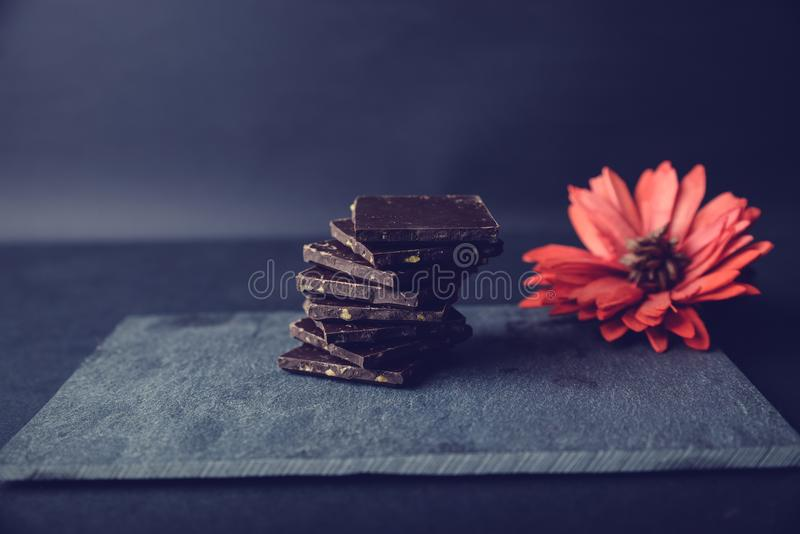 Dark chocolate on stone colored with red flower. Pieces of dark chocolate on stone. Appetizing and colorful. Just perfect for Valentines Day royalty free stock photography