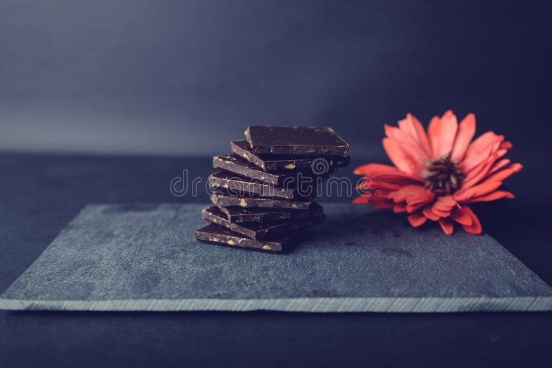 Dark chocolate on stone colored with red flower. Pieces of dark chocolate on stone. Appetizing and colorful. Just perfect for Valentines Day royalty free stock photo