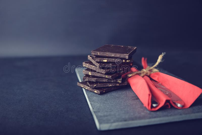 Dark chocolate on stone colored with red flower. Pieces of dark chocolate on stone. Appetizing and colorful. Just perfect for Valentines Day stock image