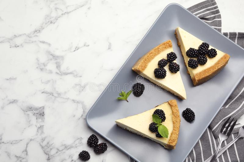 Pieces of delicious cheesecake with blackberries on white marble background. Space for text. Pieces of delicious cheesecake with blackberries on white marble stock photo