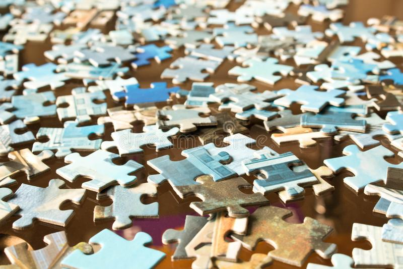 Pieces of different puzzles on a glass table. Conceptual abstract image. Selective focus stock photos
