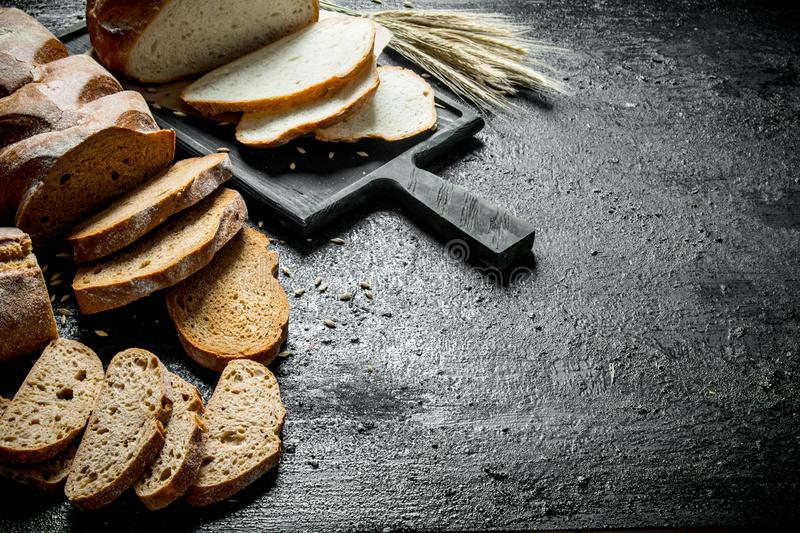Pieces of different types of bread. On black rustic background stock images