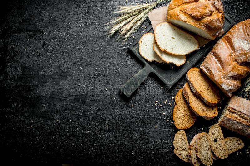 Pieces of different types of bread. On black rustic background royalty free stock photography