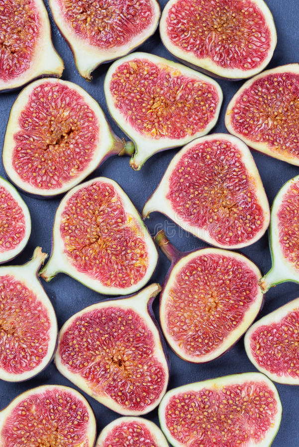 Pieces of fig on a stone board. Fruit background royalty free stock image
