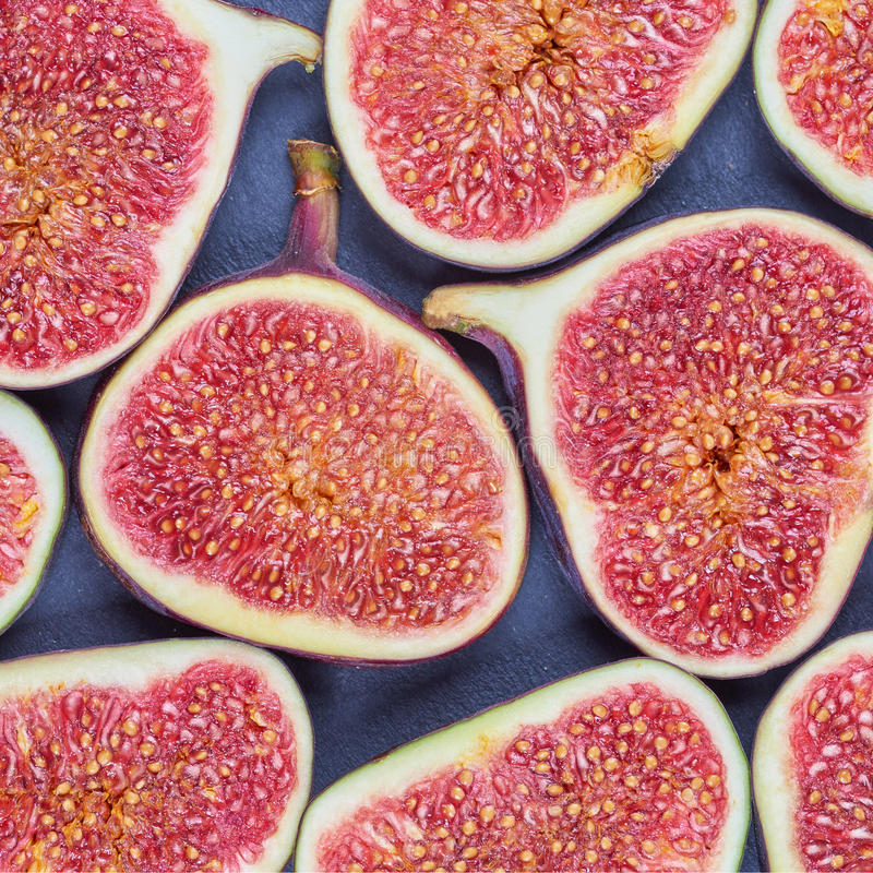 Pieces of fig on a stone board. Fruit background stock images