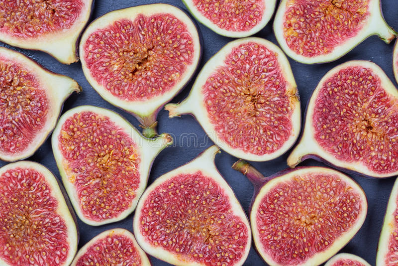 Pieces of fig on a stone board. Fruit background stock photography