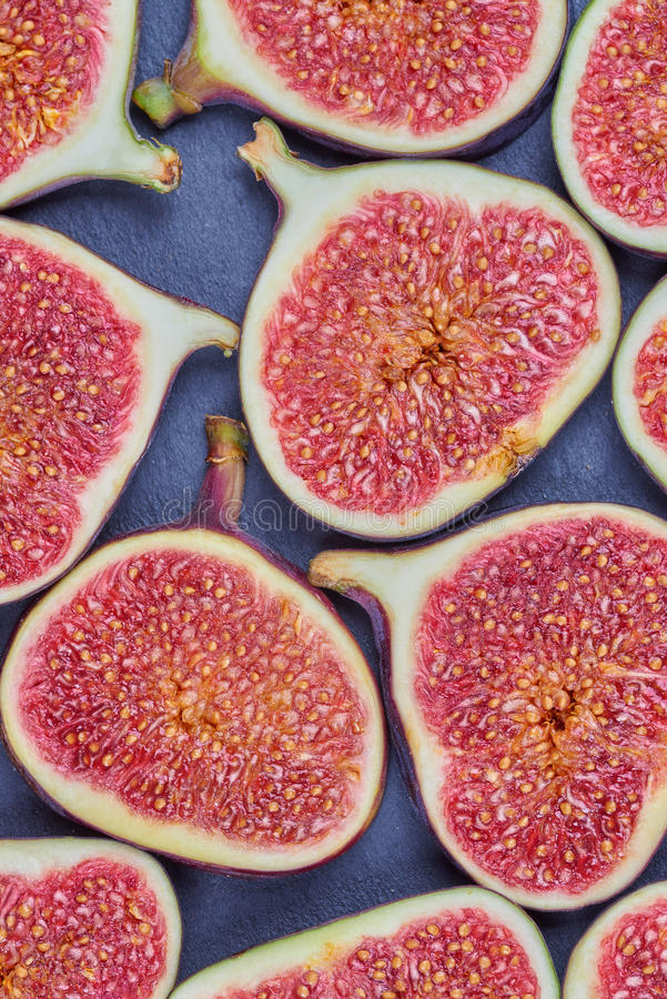 Pieces of fig on a stone board. Fruit background stock photo