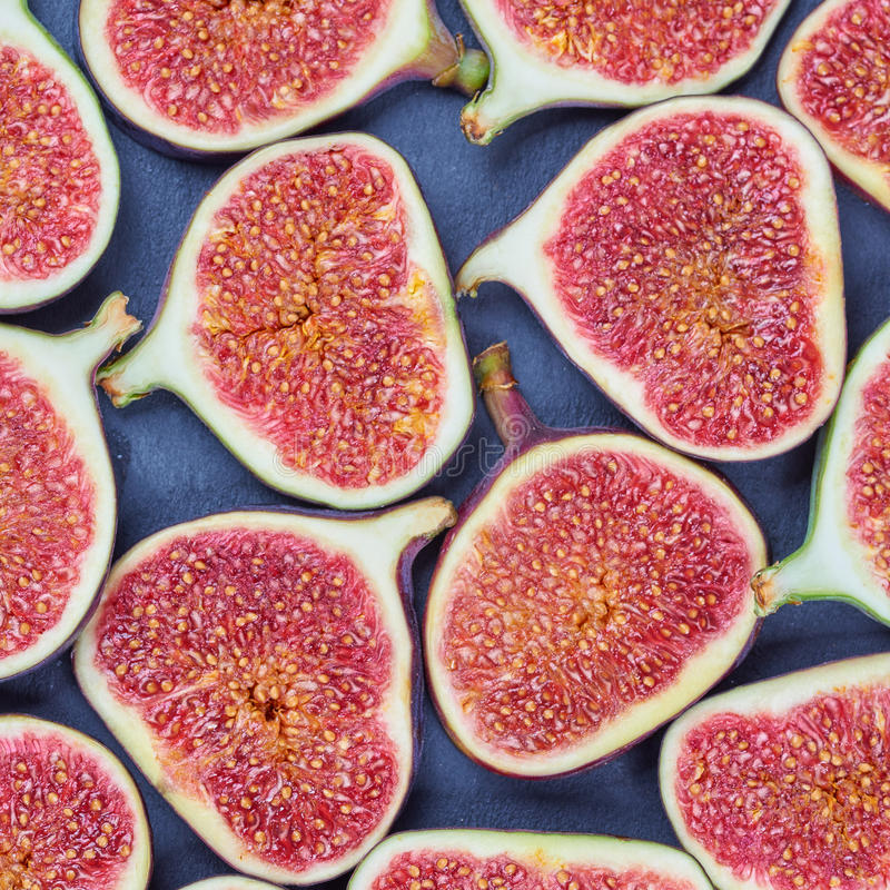 Pieces of fig on a stone board. Fruit background royalty free stock photography