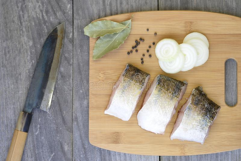 Pieces of fish on a cutting Board with spices on a wooden rustic vintage background with a kitchen knife stock images