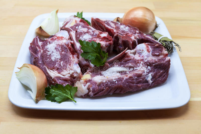 Pieces of fresh lamb on the plate . Delicious fat-tailed lamb with onion on the plate . Meat to be grilled. royalty free stock image
