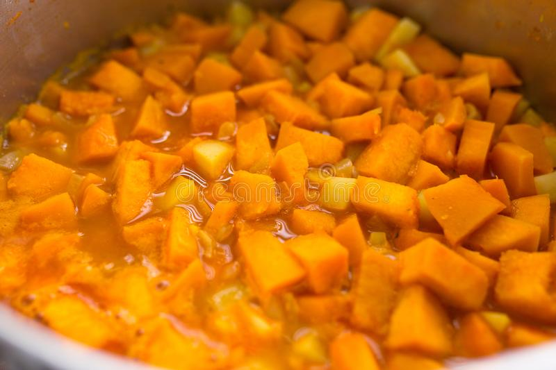 Pieces of fresh pumpkin in the pot for a pumpkin soup stock images