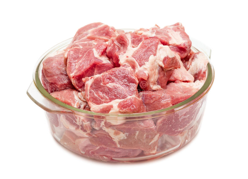 Pieces of fresh raw meat in glass pan. Isolated on white background stock images