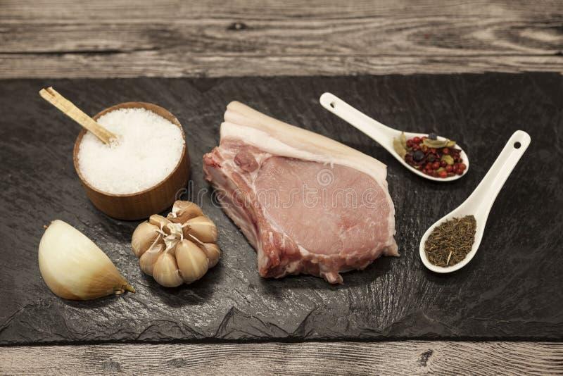 Pieces of fresh raw pork onion, garlic, spices, salt on the stone plate.  stock photos