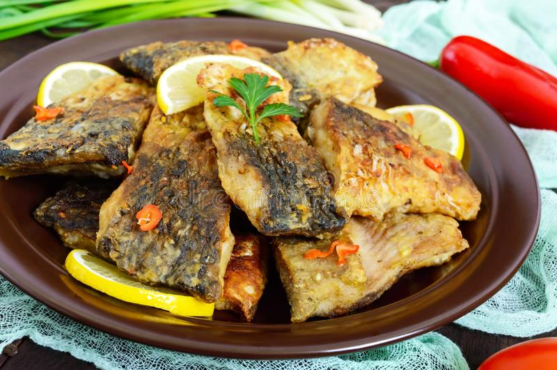 Pieces of fried fish carp on a ceramic plate stock photos