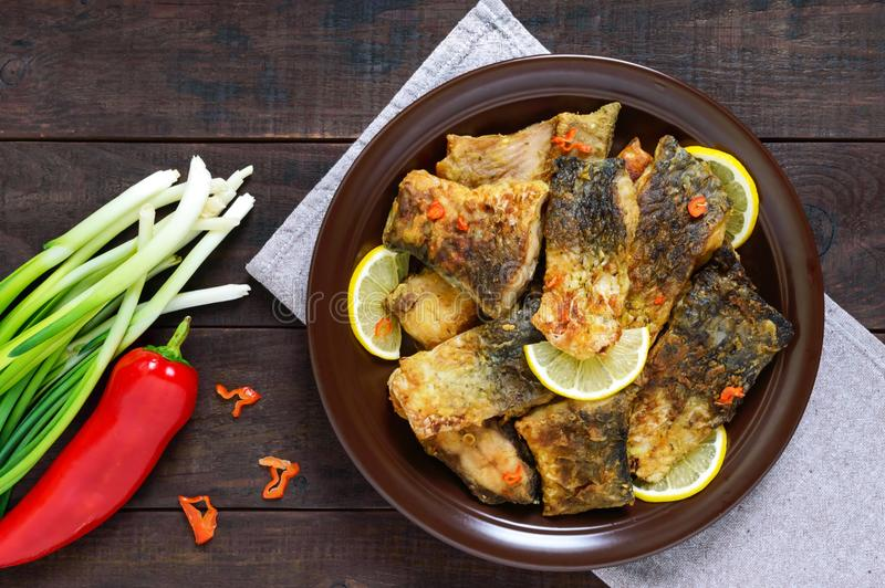 Pieces of fried fish carp on a ceramic plate on a dark wooden background. royalty free stock photos