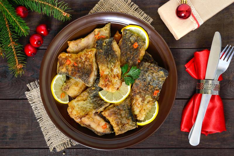 Pieces of fried fish carp on a ceramic plate on a dark wooden background stock photo
