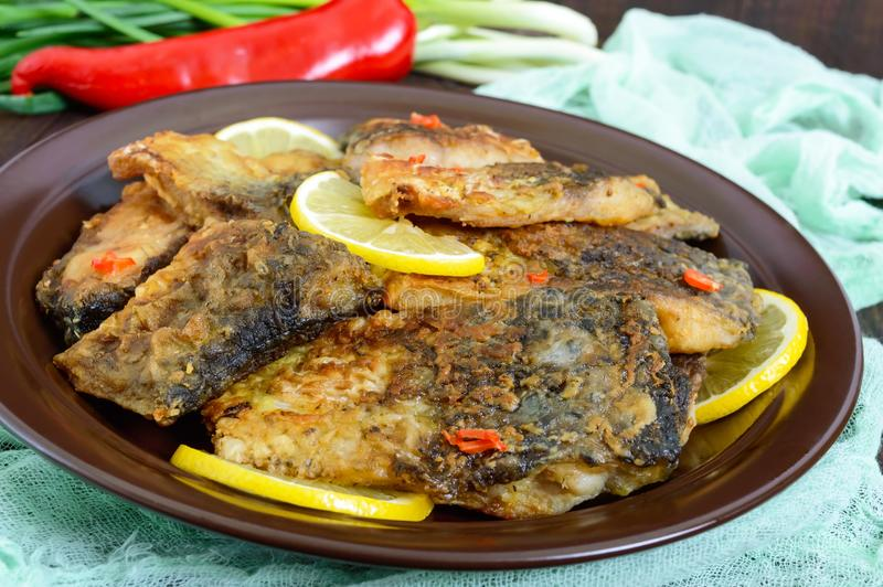 Pieces of fried fish carp on a ceramic plate stock photography