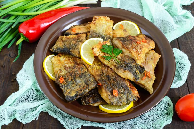 Pieces of fried fish carp on a ceramic plate royalty free stock images