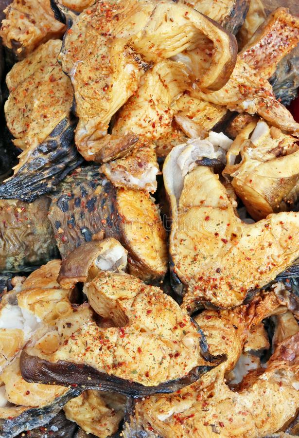 Pieces of grilled smoked fish trout with spices and pepper stock images